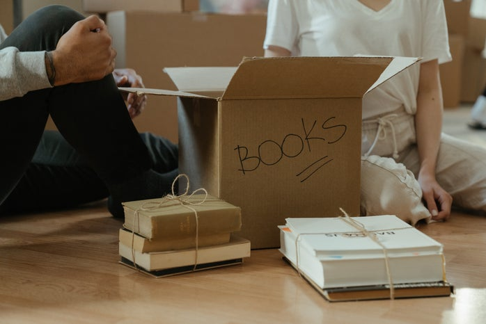 Box of books with humans on floor