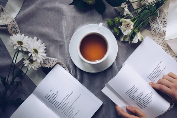 person reading poetry books next to tea and flowers