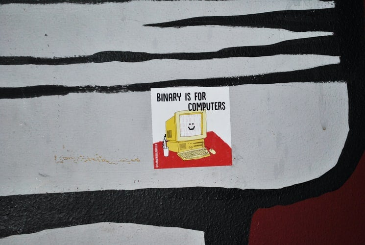 """poster pasted on a black, white and dark red wall written """"binary is for computers"""""""