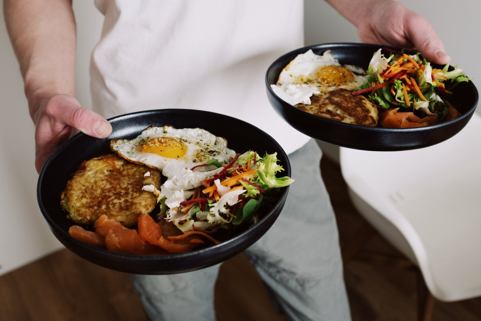 A man holding two plates of food; there is egg, a salad of some kind, and what looks to be potato and bacon.