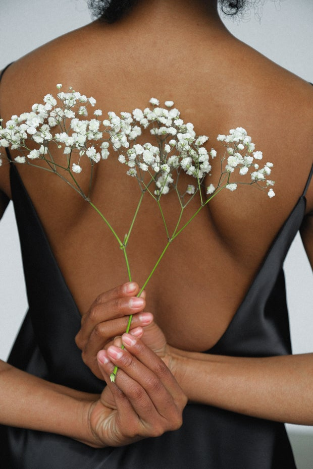 Black woman holding flowers behind back
