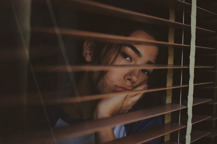 sad young woman looking out window