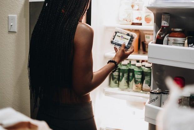 Woman grocery shopping, opening her fridge