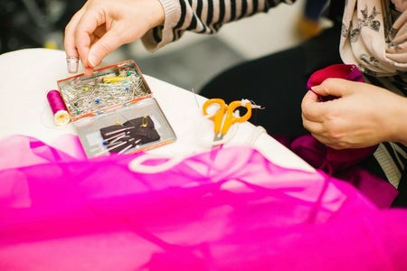 Person (seamstress) holding pin at work with fabric