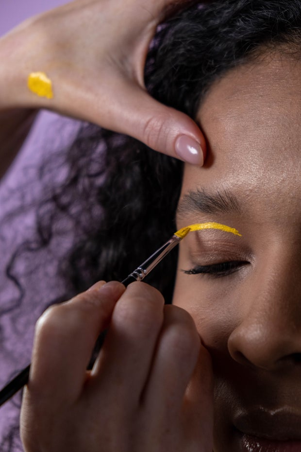 Woman applying colorful eyeliner