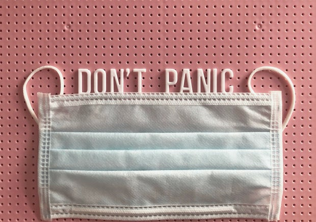"""reuseable surgical mask with phrase """"don't panic"""" on a pink letter board"""
