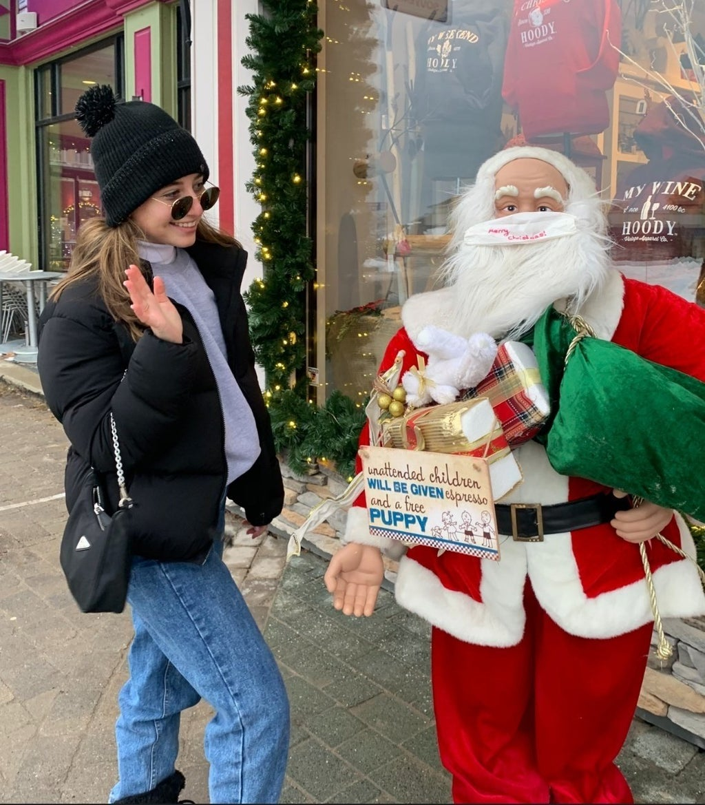 Girl standing with a santa claus statue outside of store; pictured are Rachel Alter, Sasha Folgoas and Daphna Roytblat