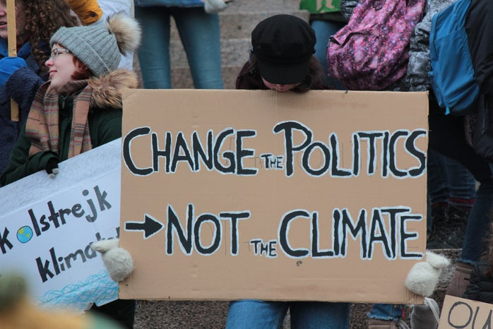 """sign reading \""""change the politics not the climate\"""" at a climate protest"""
