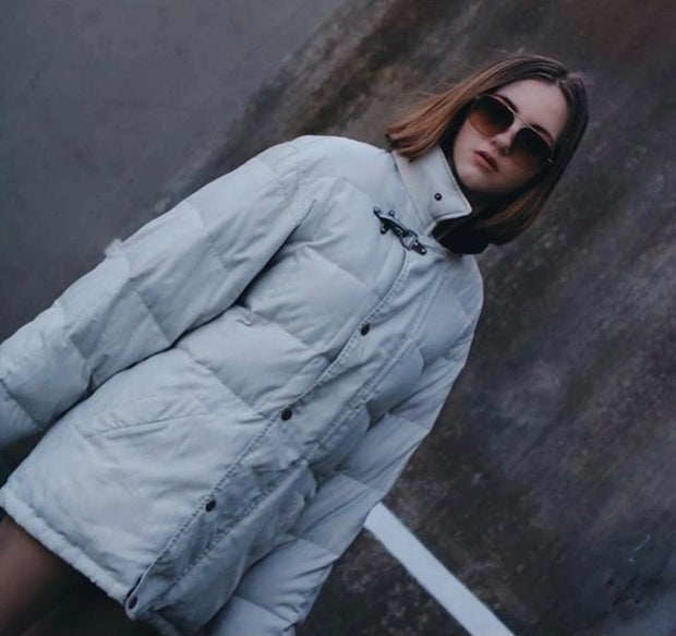 young woman wearing light blue jacket