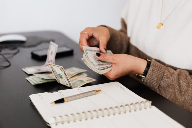 payroll clerk counting money while sitting at table