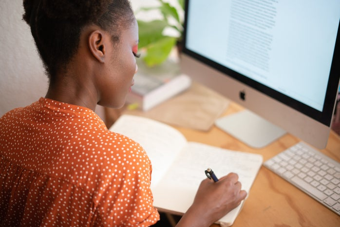 Black woman writing at computer desk writing in journal notebook write natural work corporate african