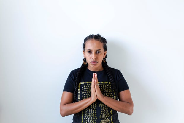 woman wearing a black shirt with gold writing with her hands held together in a prayer pose