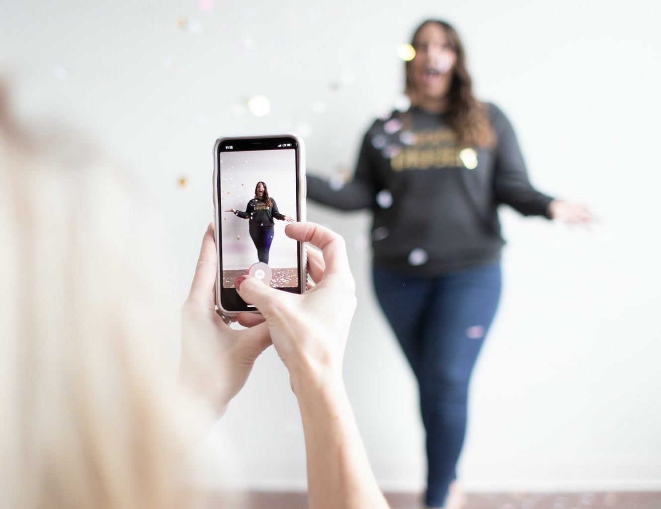 woman filming vertical video of woman throwing confetti