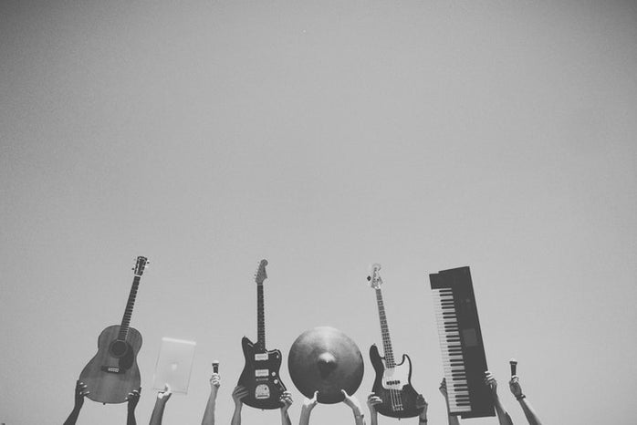 hands holding guitars, microphones, and piano keyboard