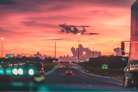 view from a windshield of the highway with a pink sky