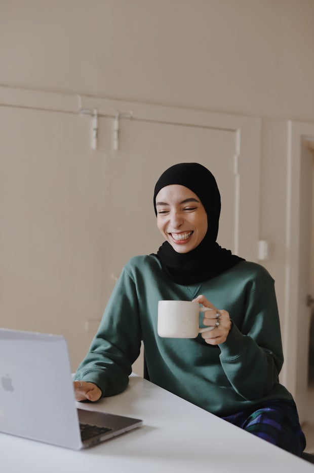 Woman laughs while holding a coffee cup and looking at her computer.