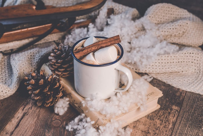 hot cocoa surrounded by a white blanket, white fluff, cinnamon sticks, and pinecones