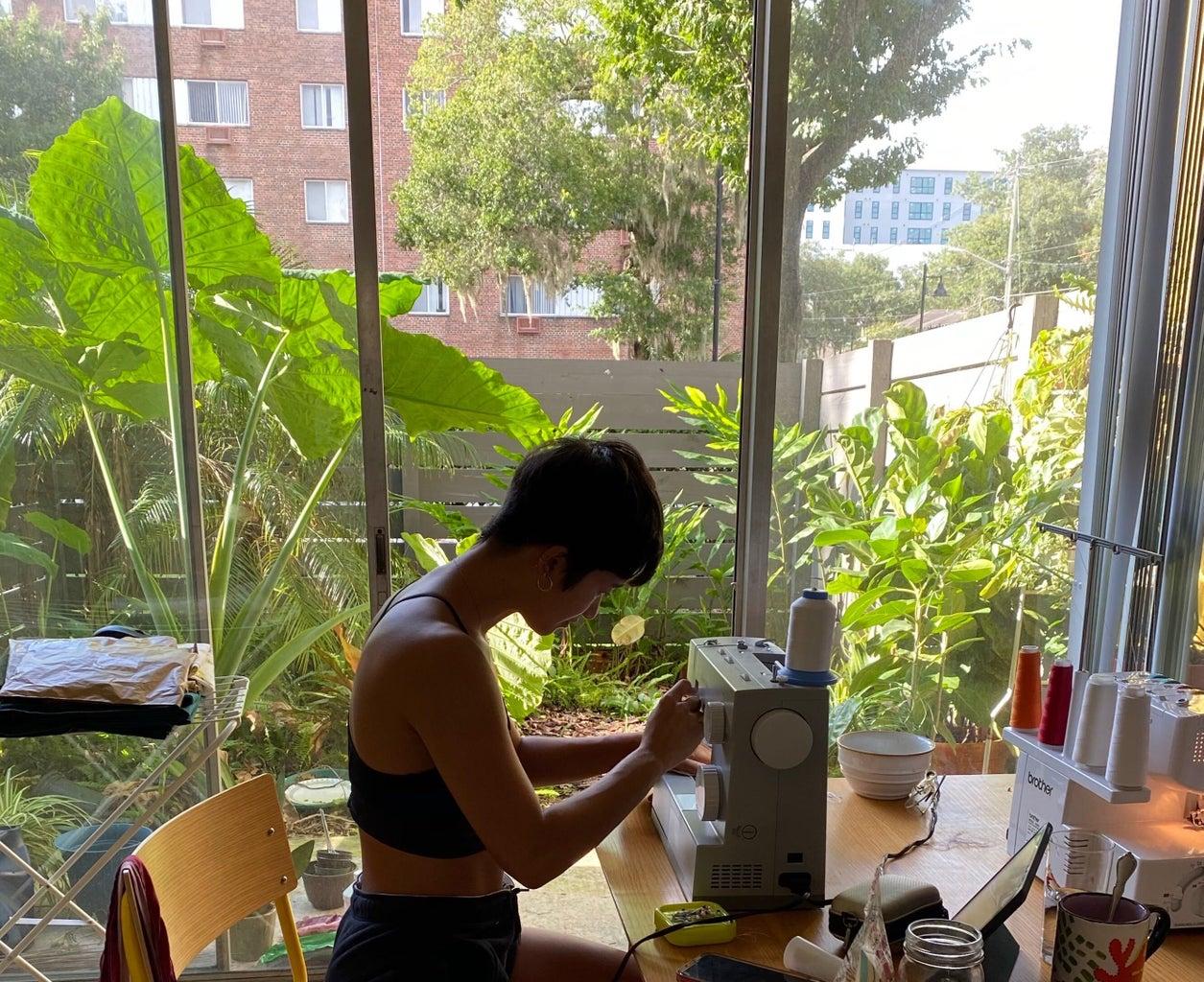 Mia Crisosto working on her sewing machine.