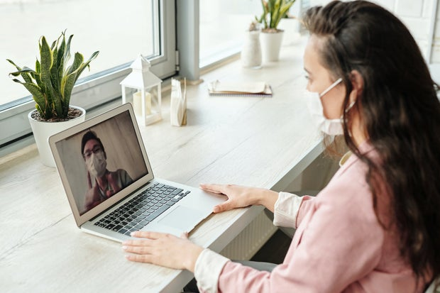 Woman in front of laptop with mask on