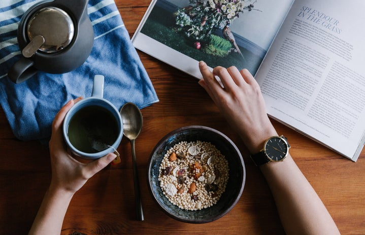 person holding a cup of tea with a bowl of nuts/grains