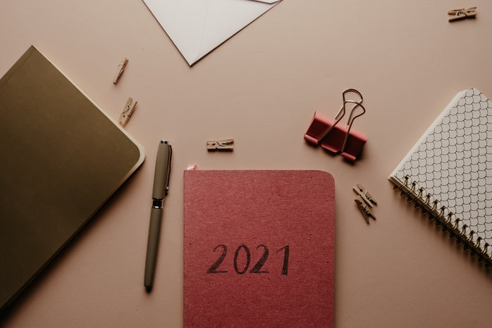 Desk with stationary, an agenda, pens, paperclips, and a binder clip