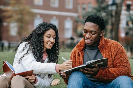 Two students sitting in the grass talking and studying LLC article