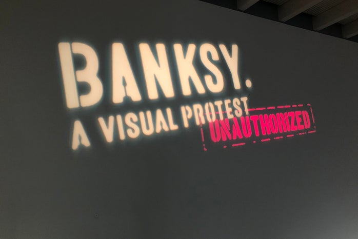 """The name of the exhibition \""""Banksy. A Visual Protest\"""" held in a Finnish museum called Art Museum Gösta. Title projected on the gallery wall."""