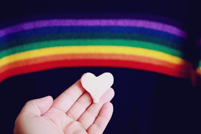 Hand holding a small heart with a rainbow in the background