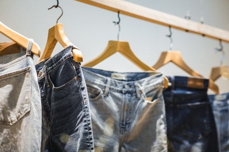 Pairs of jeans hung up on clothing rack