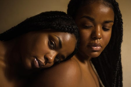 two Black women with one leaning her head on the other