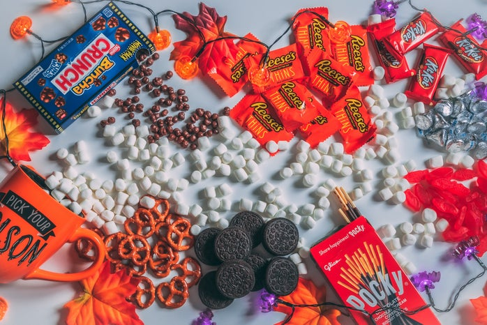 Candy and Halloween decorations are spread across a table.